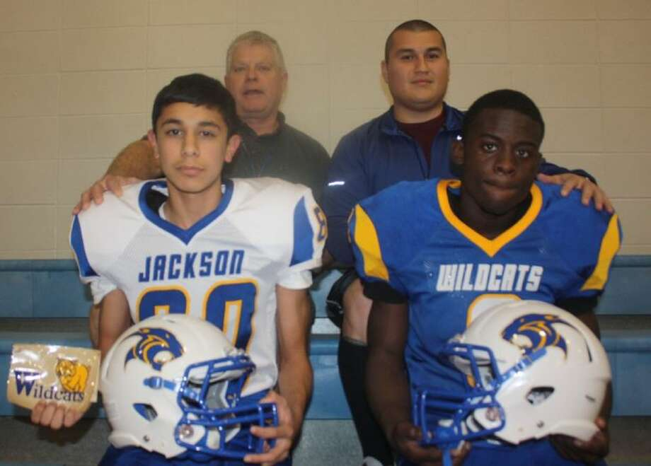 The Jackson Intermediate coaches join two players modeling the team's new uniforms and helmets that was bought through the genorosity of the Justin J. Watt Foundation. Photo: Robert Avery