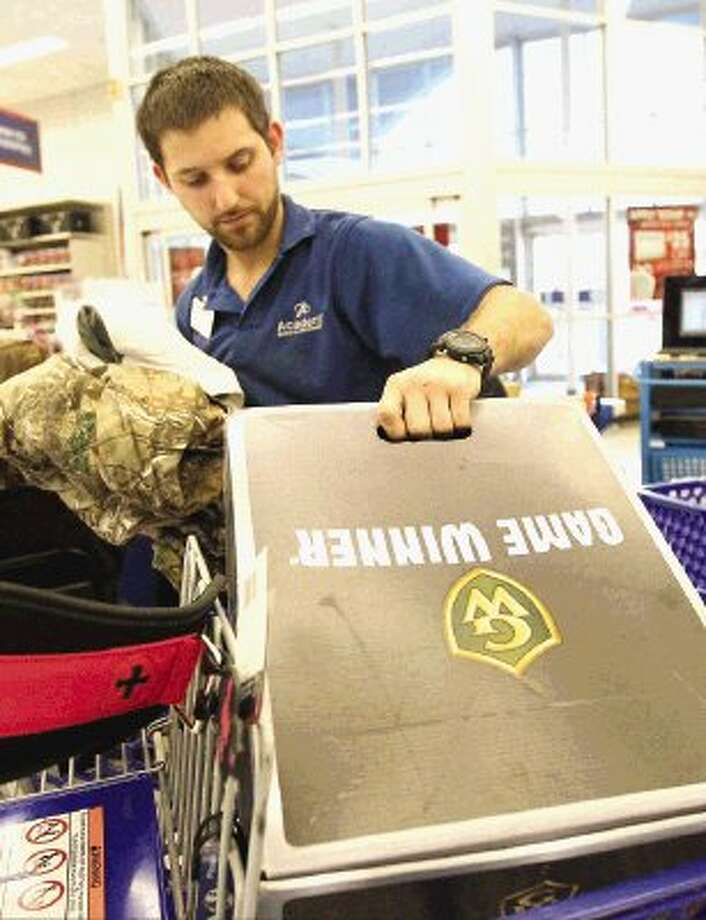 An Academy employee sorts returned items at Academy Sports + Outdoors in Conroe Friday. Photo: Staff Photo By Jason Fochtman