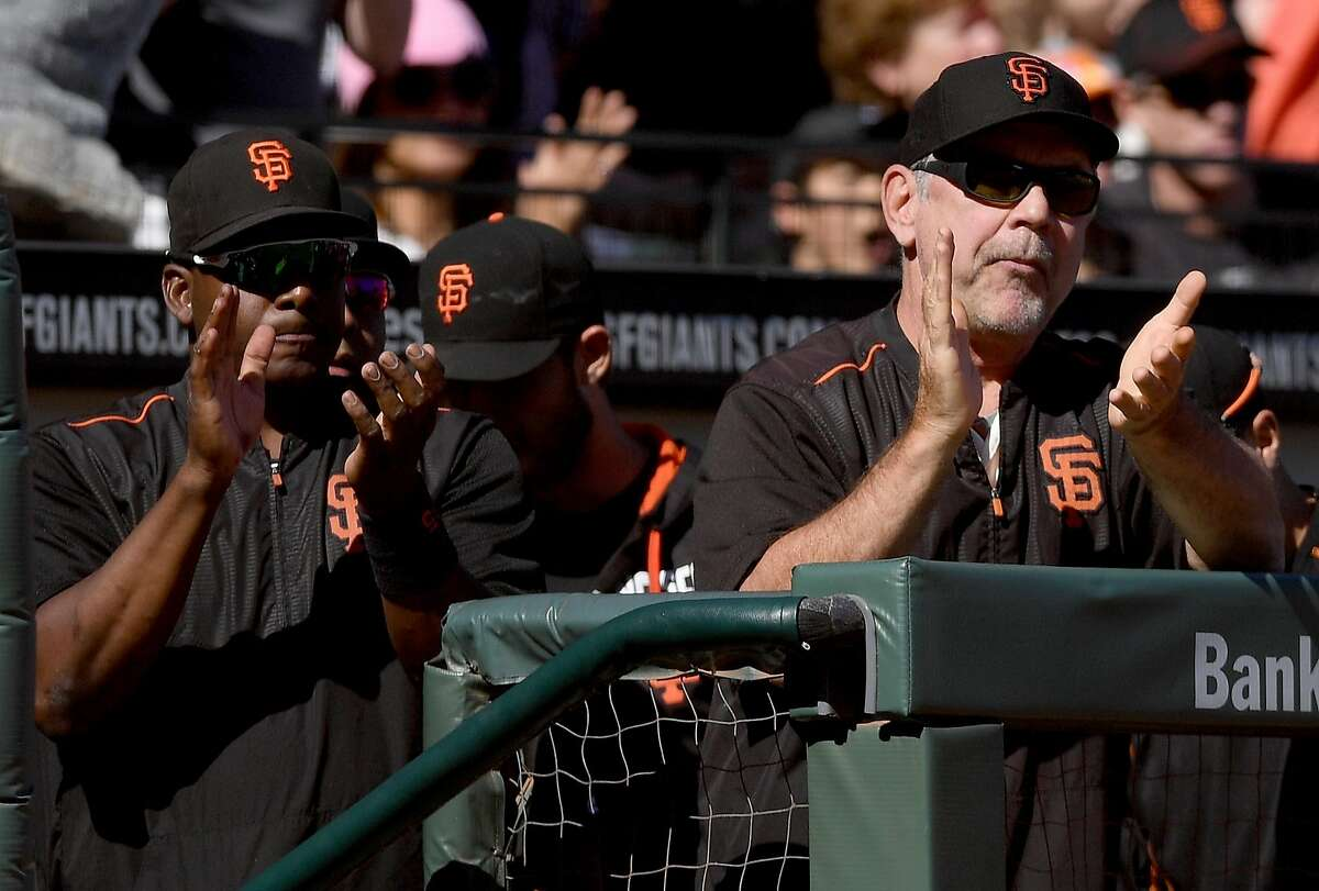 Hitting coach Hensley Meulens (left) and manager Bruce Bochy of the San Francisco Giants celebrate after the Giants scored a run against the Los Angeles Dodgers in the bottom of the seventh inning at AT&T Park on October 1, 2016 in San Francisco.