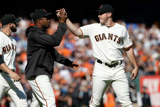 Starting Ty Blach, (right) gets a high five from Santiago Casilla at the end of the game, as the San Francisco Giants beat the Los Angeles Dodgers 3-0at AT&T Park  in San Francisco, California , on Sat. Oct. 1, 2016.