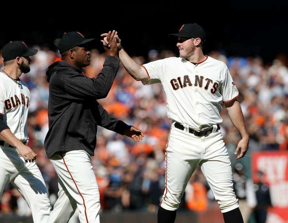 Starting Ty Blach, (right) gets a high five from Santiago Casilla at the end of the game, as the San Francisco Giants beat the Los Angeles Dodgers 3-0at AT&T Park  in San Francisco, California , on Sat. Oct. 1, 2016. Photo: Michael Macor, The Chronicle