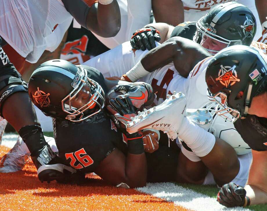 Oklahoma State running back Barry J. Sanders (26) pushes through for a touchdown against Texas in the third quarter of an NCAA college football game in Stillwater, Okla., Saturday, Oct. 1, 2016. Oklahoma State won 49-31. (AP Photo/Sue Ogrocki) Photo: Sue Ogrocki, STF / Associated Press / AP2016