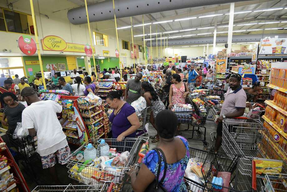 Residents stock up on groceries and supplies Saturday in Portmore, Jamaica, in advance of the arrival of Hurricane Matthew. The storm is forecast to pass near the region late Monday. Photo: RICHARDO MAKYN, AFP/Getty Images