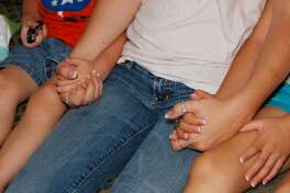 A young mother sits hand in hand with her children after seeking help at the Montgomery County Women's Center.