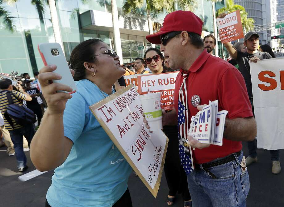 Bertha Sanles, of Miami, left, shouts at Bobby Mayo, of Boca Raton, Fla., a supporter of Republican presidential candidate Donald Trump, as she protests outside of a campaign rally attended by Trump, Friday, Sept. 16, 2016, in Miami. Sanles is an undocumented immigrant who says she pays taxes, and believes Trump should release his tax returns. (AP Photo/Lynne Sladky) Photo: Lynne Sladky, Associated Press