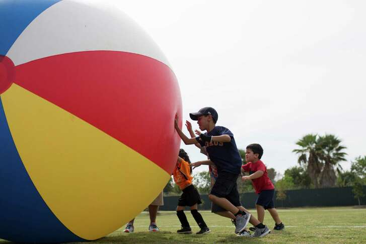 Joaquin Davila, center, 6, Elisa Davila, 3, and Julian Vazquez, right, 3, push a giant ball as part of the games organized as part of the 100 Year Park Anniversary Celebration Grand Opening Of Gragg Park, Saturday, Oct. 1, 2016, in Houston.