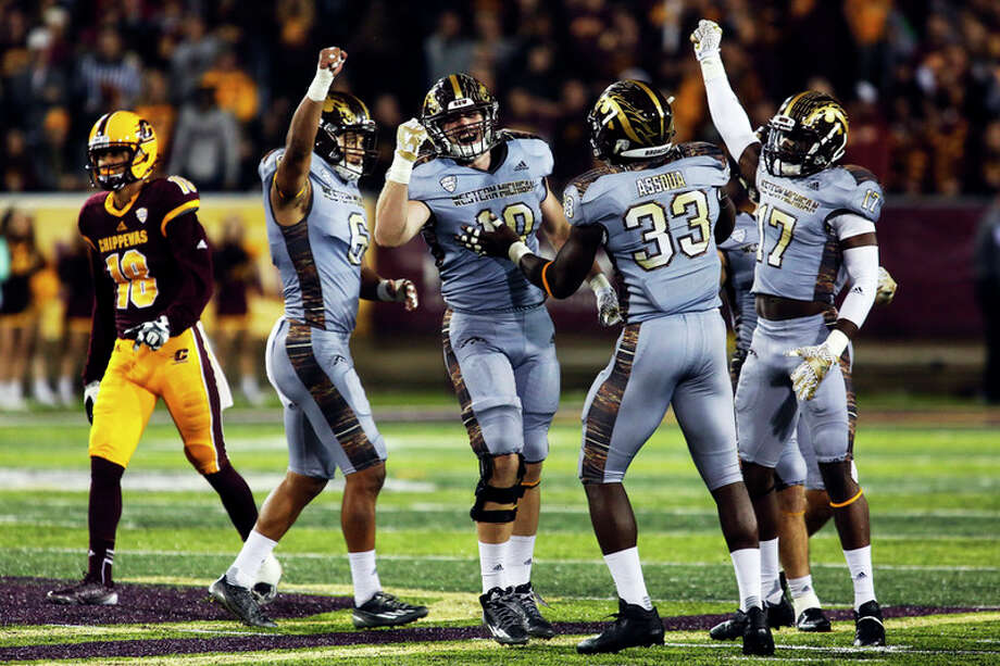 THEOPHIL SYSLO | For the Daily News Western Michigan University defenders celebrate after nearly intercepting the ball on fourth down in Saturday night's game against Central Michigan University at the Kelly/Shorts Stadium.
