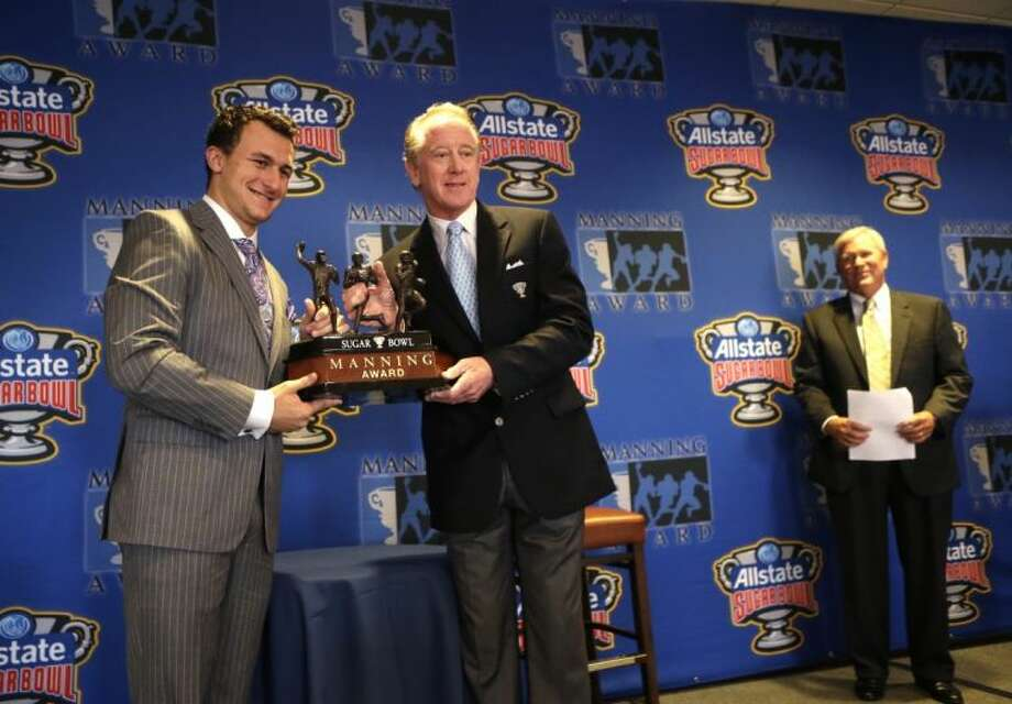 Heisman Trophy winner and Texas A&M quarterback Johnny Manziel poses with former NFL quarterback Archie Manning and the the Manning Award on Thursday in New Orleans. At right is New Orleans sportscaster Jim Henderson.