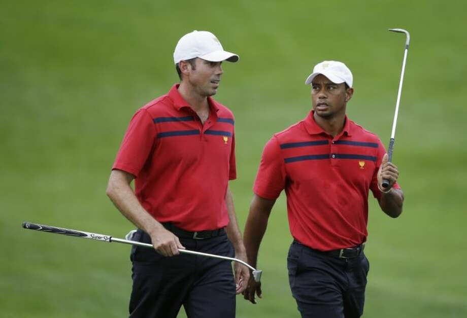 Matt Kuchar, left, talks with Tiger Woods as they walk to the 16th green during a fourball match at the Presidents Cup at Muirfield Village Golf Club on Saturday in Dublin, Ohio. Woods and Kuchar defeated Adam Scott and Hideki Matsuyama 1-up.