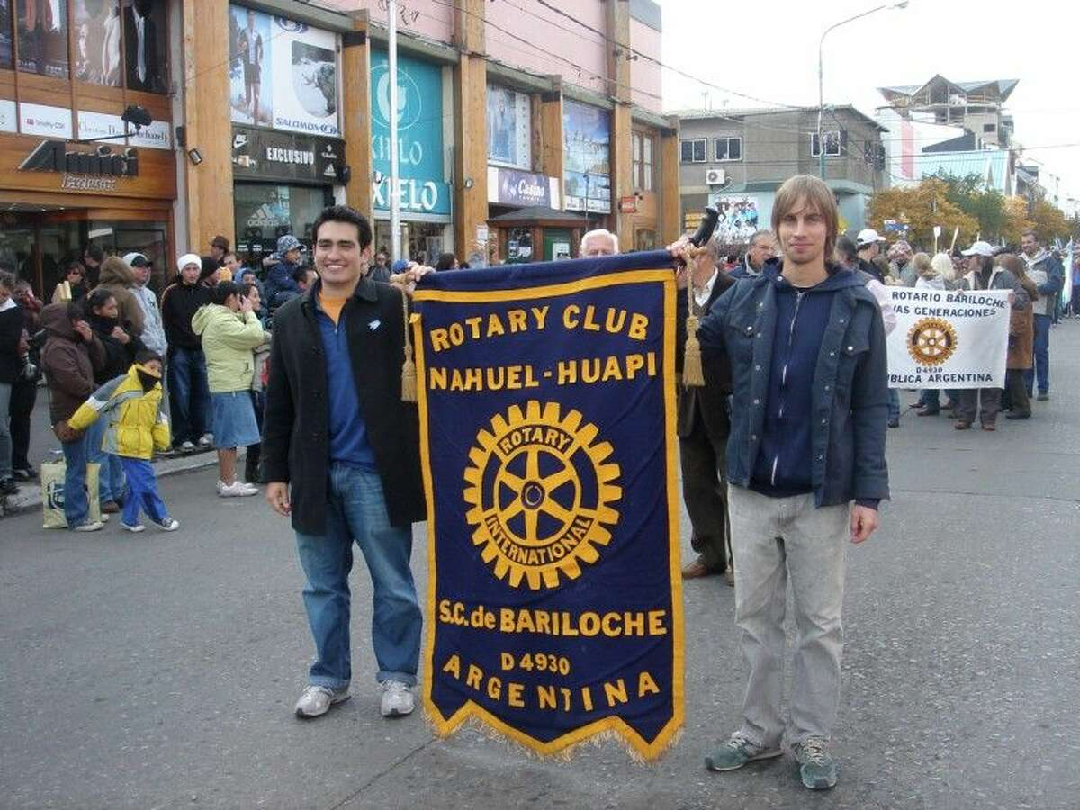 Tom Mendez, the Kingwood Rotary club's 2009-2010 Rotary Ambassadorial Scholar, left of the Rotary flag which he was carrying in a community parade in Buenos Aires.