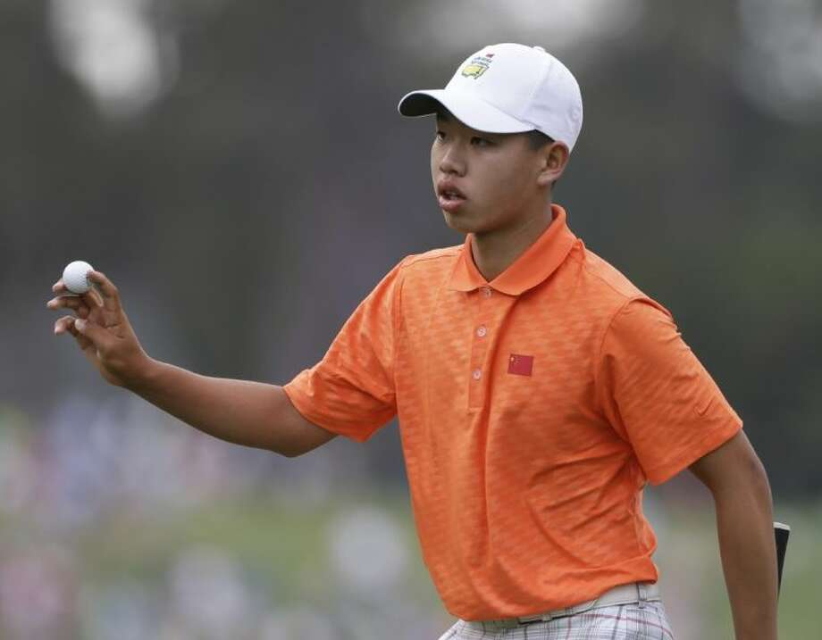 Amateur Guan Tianlang, of China, holds up his ball after putting on the first green during the second round of the Masters golf tournament Friday in Augusta, Ga.