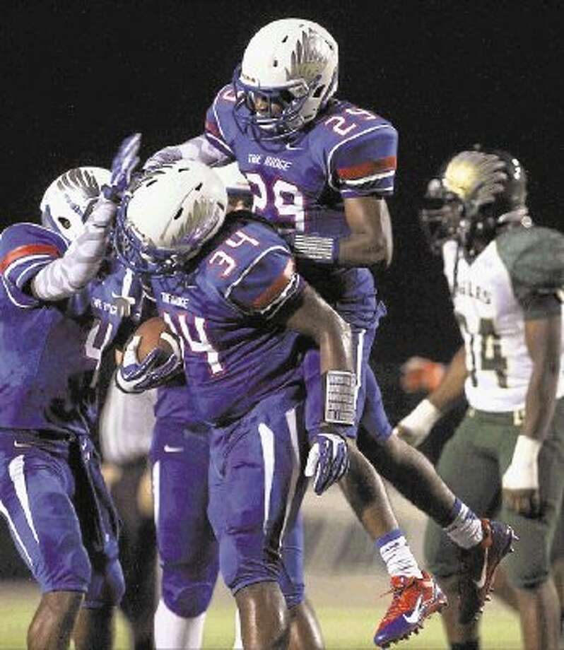 Justin Edwards (34) and his Oak Ridge teammates, including J.D. Hurd (4) and Llewelldyn Jones (29), have had plenty to celebrate during the team's 5-0 start. The War Eagles edged Bryan 36-33 on Friday night. / @WireImgId=2640670