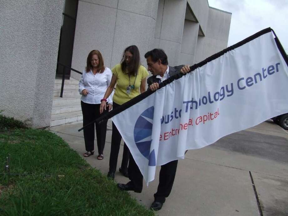 Pictured, right to left, Tim Budzik, Jane Lea Hicks and Evelyn Boatman plant the Houston Technology Center's banner at their government shutdown location, across the street from the Johnson Space Center. Photo: JEFF NEWPHER