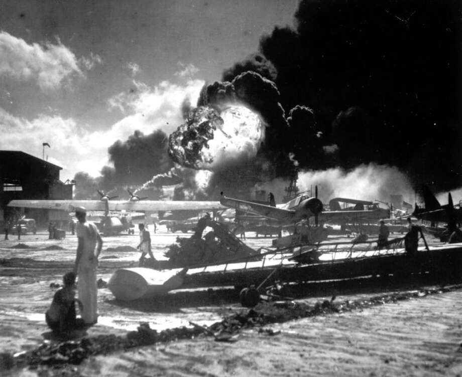 In this Dec. 7, 1941 file photo provided by the U.S. Navy, sailors stand among wrecked airplanes at Ford Island Naval Air Station as they watch the explosion of the USS Shaw in the background, during the Japanese surprise attack on Pearl Harbor, Hawaii.