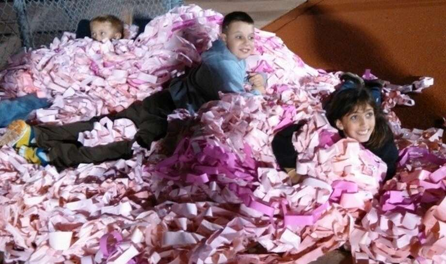 """Battle of the Bell Goes Pink"": Greenleaf Elementary students Ryan McGuire, CJ Sever and Amberlee Miller enjoy the ""Pink Link"" pile."
