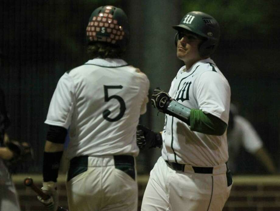 The Woodlands' Brandon Miles score a run in the third inning as teammate Hillin Warren congratulates him during a District 14-5A high school baseball game on Friday. The Woodlands defeated Oak Ridge 8-0. To view or order this photo, or others like it, visit: HCNPics.com.