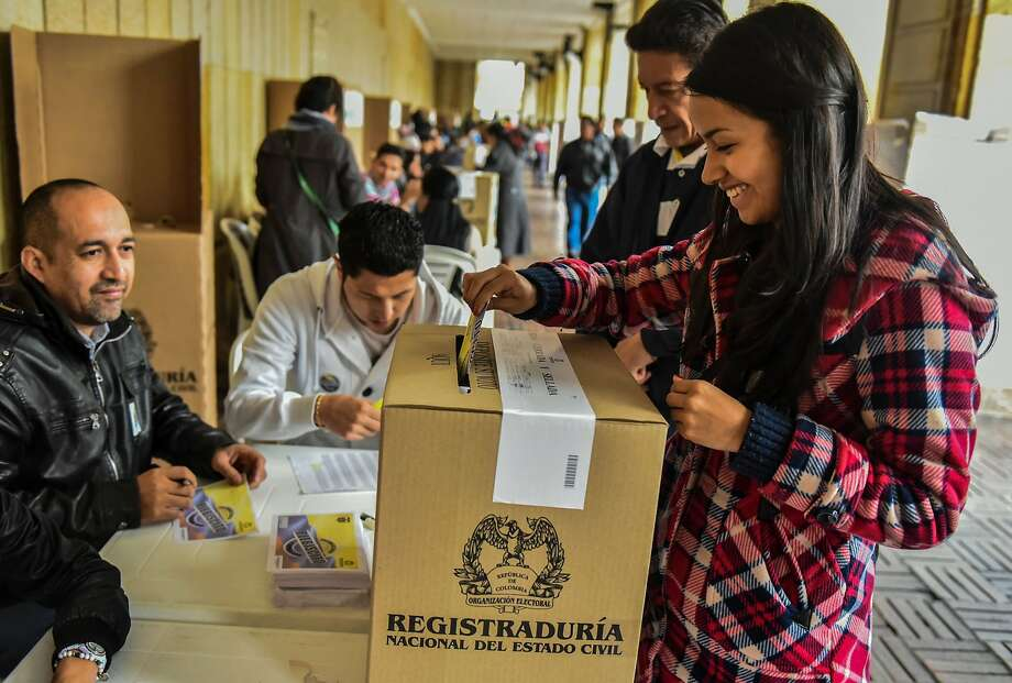 A resident casts her vote in Bogota, Colombia, on a referendum asking whether a peace accord with rebels should be ratified. The pact would end a 52-year war with the communist rebels. Photo: LUIS ACOSTA, AFP/Getty Images