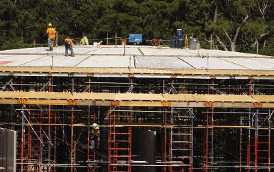 Workers construct two large water tanks that can hold 5 million gallons each as part of the water purification process at the Lake Conroe Surface Water Pilot Plant June 3. The site is part of Montgomery County's Groundwater Reduction Plan, which will reduce the county's reliance on groundwater by providing water from Lake Conroe. The plan is part of a state program mandated by the Lone Star Groundwater Conservation District, which will require the state to reduce groundwater usage to 70 percent of its 2009 levels. / Conroe Courier