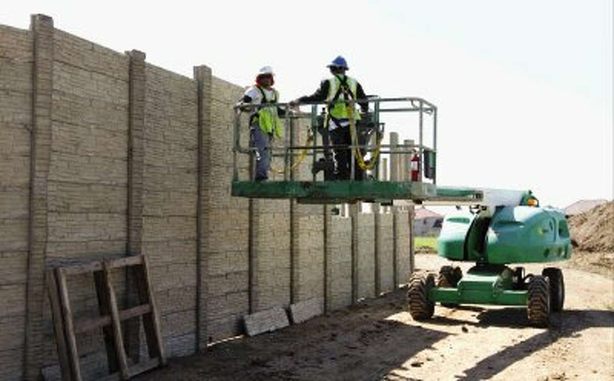 Workers build a sound wall around a construction site at the Lake Conroe Surface Water Pilot Plant June 3.