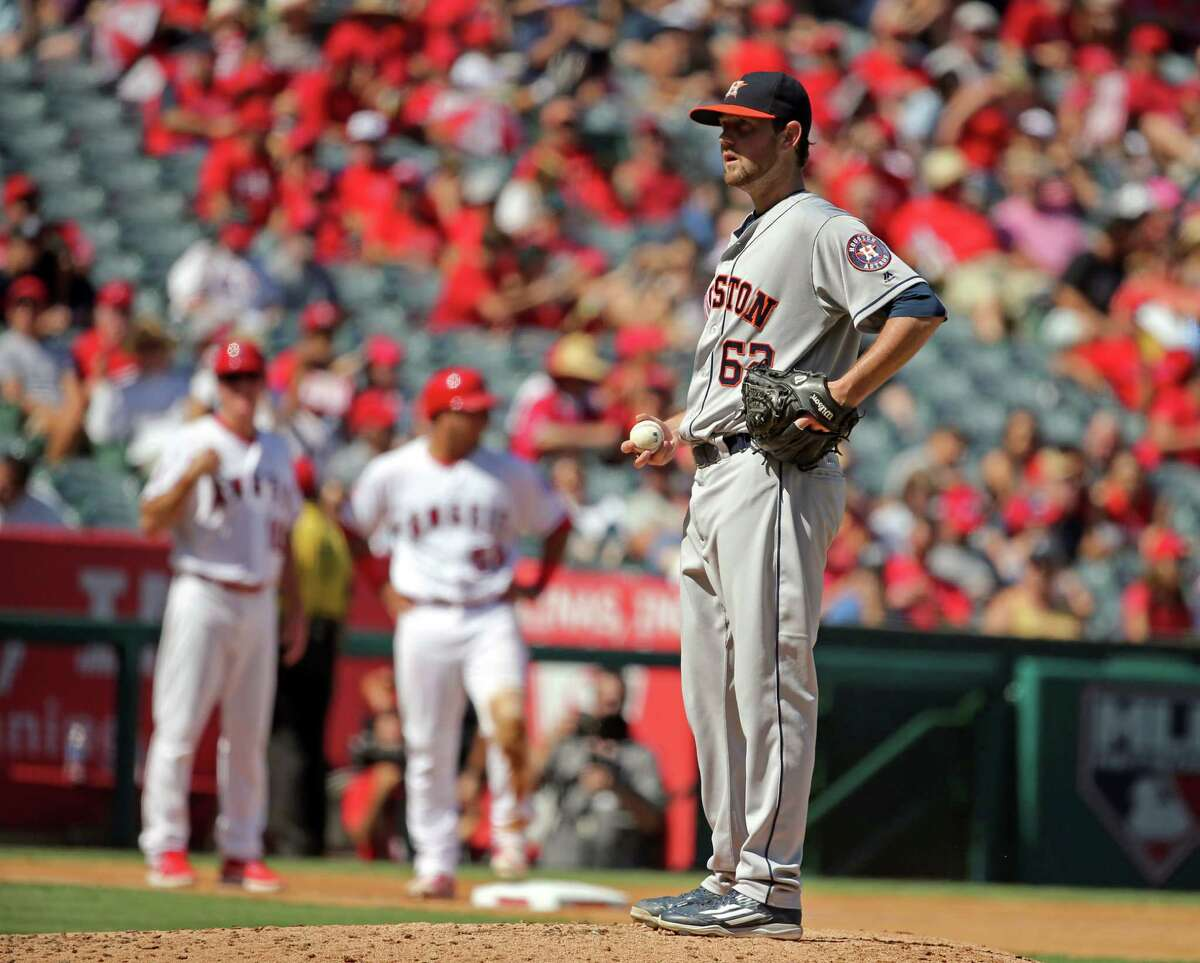 Houston Astros starting pitcher Brady Rodgers, right, waits as manager A.J. Hinch walks to the mound to take him out of a baseball game against the Los Angeles Angels in the fourth inning in Anaheim, Calif., Sunday, Oct. 2, 2016. (AP Photo/Reed Saxon)