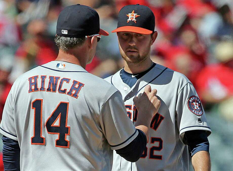 Houston Astros manager A.J. Hinch, left, takes the ball from starting pitcher Brady Rodgers in the fourth inning of a baseball game against the Los Angeles Angels in Anaheim, Calif., Sunday, Oct. 2, 2016. (AP Photo/Reed Saxon) Photo: Reed Saxon, Associated Press / Copyright 2016 The Associated Press. All rights reserved. This material may not be published, broadcast, rewritten or redistribu