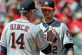 Houston Astros manager A.J. Hinch, left, takes the ball from starting pitcher Brady Rodgers in the fourth inning of a baseball game against the Los Angeles Angels in Anaheim, Calif., Sunday, Oct. 2, 2016. (AP Photo/Reed Saxon)