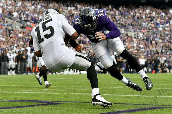 BALTIMORE, MD - OCTOBER 2:  Eric Weddle #32 of the Baltimore Ravens hits Michael Crabtree #15 of the Oakland Raiders in the end zone in the fourth quarter at M&T Bank Stadium on October 2, 2016 in Baltimore, Maryland. (Photo by Larry French/Getty Images)