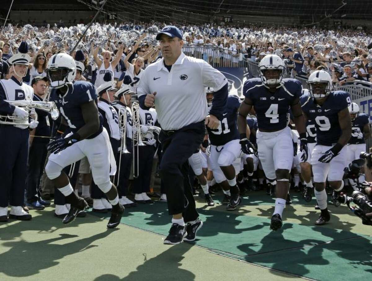 Penn State coach Bill O'Brien leads his team on to the field at Beaver Stadium for a game against Eastern Michigan on Sept. 7 in State College, Pa. Two people familiar with the negotiations said Tuesday night that O'Brien has reached an agreement to coach the Houston Texans. The people spoke to The Associated Press on the condition of anonymity because an official announcement hasn't been made.