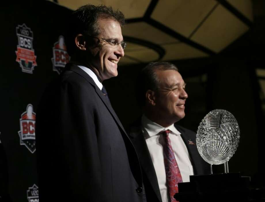 Auburn coach Gus Malzahn, left, and Florida State's Jimbo Fisher pose with The Coaches' Trophy during a news conference for the NCAA BCS national championship game.