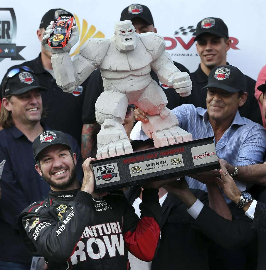 Martin Truex Jr. holds up the formidable-looking trophy he won for winning Dover International Speedway. Photo: Mel Evans, Associated Press