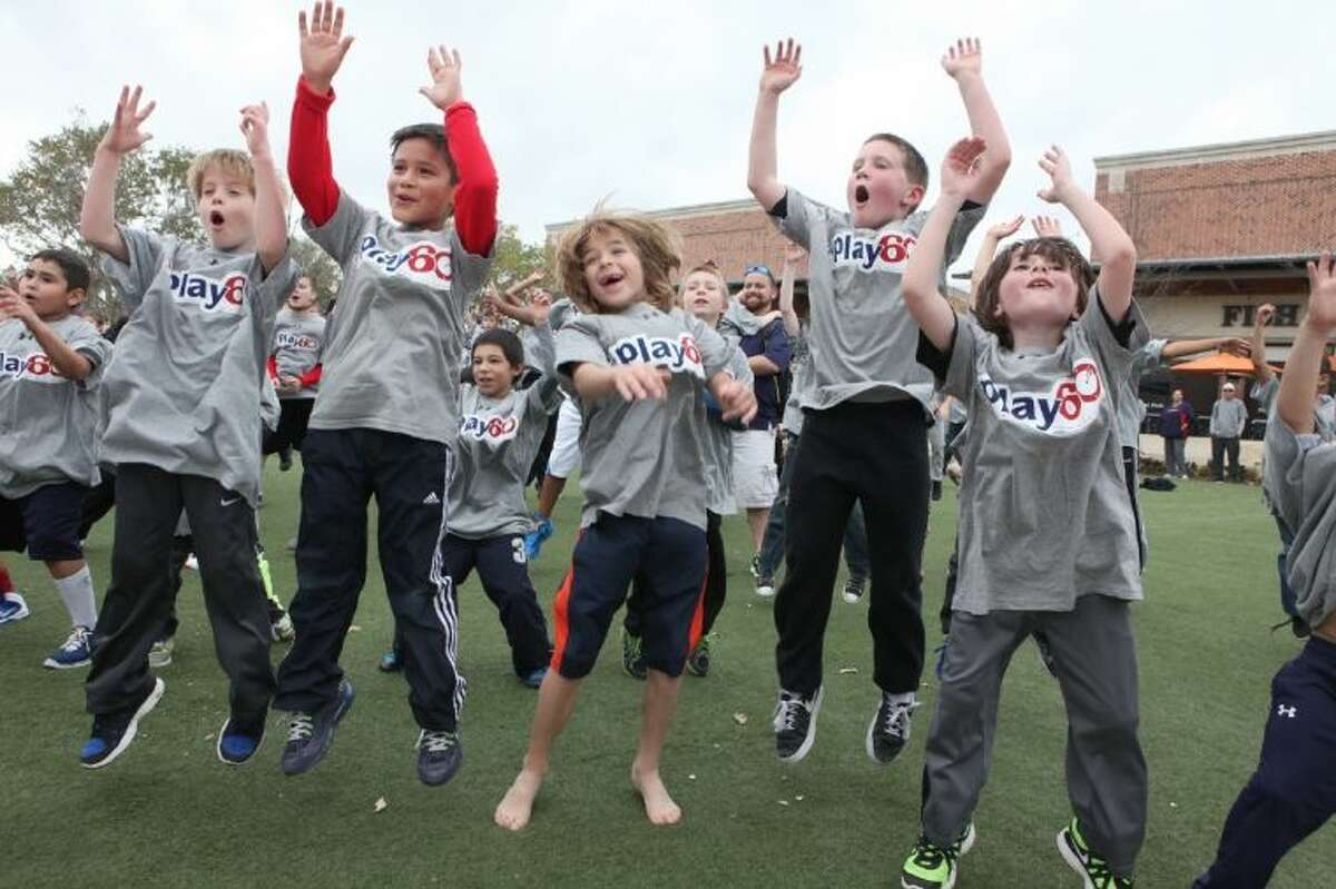 Children jump in the air as they exercise Saturday in the NFL Play 60 event on Central Green in LaCenterra at Cinco Ranch in Katy.