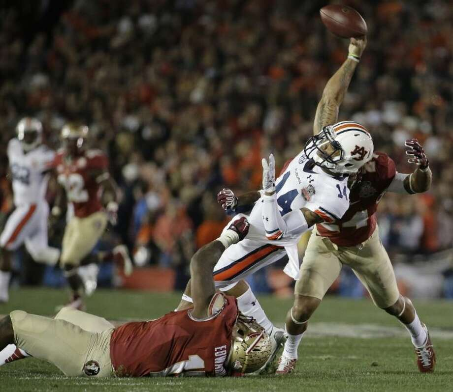 Auburn quarterback Nick Marshall (14) throws as he is hit by Florida State's Mario Edwards and Terrance Smith (24) during the first half of the NCAA BCS National Championship game. Florida State won 34-31.