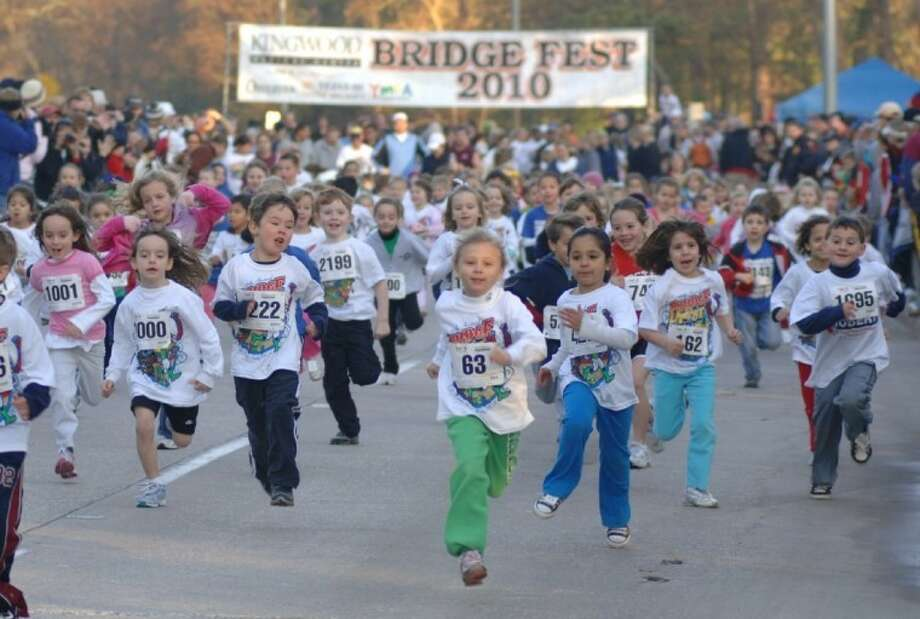Young runners make their way down West Lake Houston Parkway past the crowds of cheering parents for a past YMCA Bridge Fest.