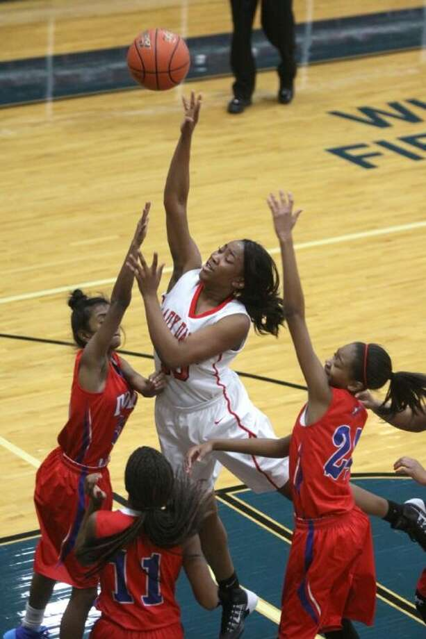 Austin's Princess Egwim shoots over the Dulles defense during their District 23-5A game Jan. 2 at Wheeler Fieldhouse in Sugar Land. The Lady Bulldogs improved to 5-0 on Jan. 4 with a win against Elkins. Visit HCNpics.com for more photos. Photo: Alan Warren