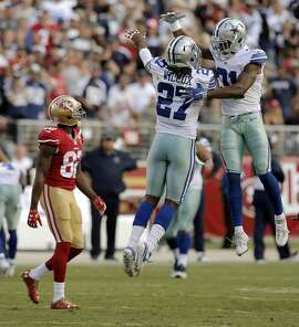 Cowboys J. J. Wilcox (27) and Byron Jones (31) celebrate as Torrey Smith (82) walks by after the 49ers could not convert on a 4th and sixth with 1:49 left in the game as the San Francisco 49ers played the Dallas Cowboys at Levi's Stadium in Santa Clara, Calif., on Sunday, October 2, 2016.