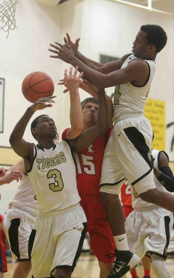 Conroe guard Stedman Bell (14) and teammate Quentin Brown battle Oak Ridge's Josh Myers (15) for a rebound during a high school boys basketball game at Conroe High School Tuesday. Oak Ridge defeated Conroe 67-57. To view or purchase this photo and others like it, visit HCNpics.com.