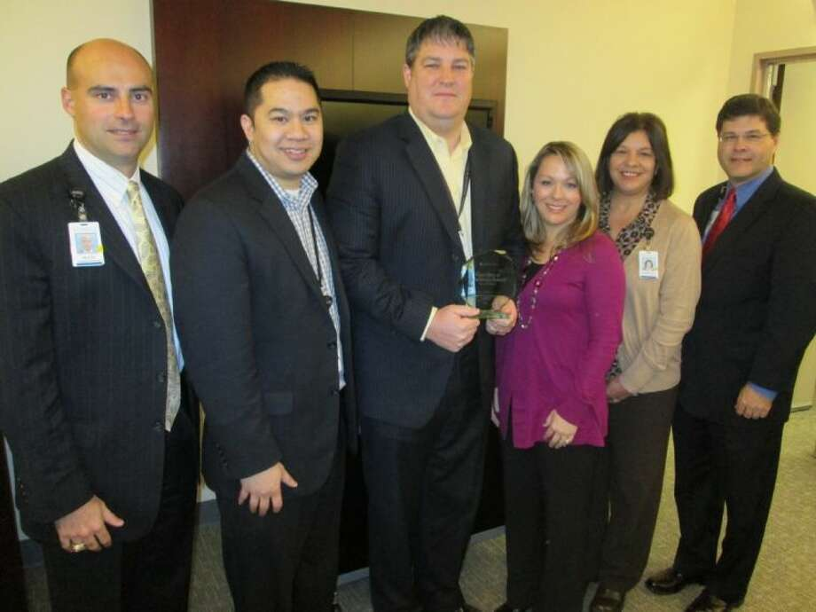 Members of the Memorial Hermann Northeast Hospital management team responsible for achieving such high patient satisfaction included, from left, Chief Operating Officer Heath Rushing; Daryl Aguirre, director of Laboratory Services; Greg Erickson, Oncology/Wound Care Service Line Administrator who is holding the prestigious award; Jessica Wooten, director of Radiology; Suzanne Croft, director of Respiratory Services; and Chief Executive Officer Louis Smith. Not pictured are Rhonda Dishongh, director of Patient Business Services/Customer Relation Management, and Susan Noe, manager of Rehabilitation Services.