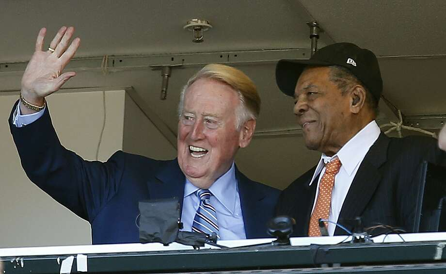 Los Angeles Dodgers announcer Vin Scully waves to fans alongside Hall of Famer baseball player Willie Mays during the fourth inning of a baseball game between the San Francisco Giants and the Los Angeles Dodgers in San Francisco, Sunday, Oct. 2, 2016. (AP Photo/Tony Avelar) Photo: Tony Avelar, Associated Press