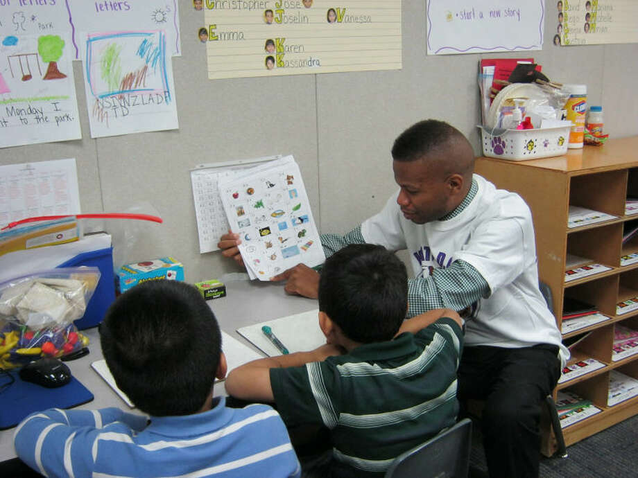 Holbrook Elementary School parent Kenneth Bailey works with kindergarten students in the classroom through Holbrook's WatchD.O.G.S. (Dads of Great Students) program, which promotes increased paternal involvement at the school. The WatchD.O.G.S. program will be recognized as the TAPE Partnership Program Crystal Award winner in the Volunteer category during the Jan. 28 awards luncheon. Photo: On 1.00