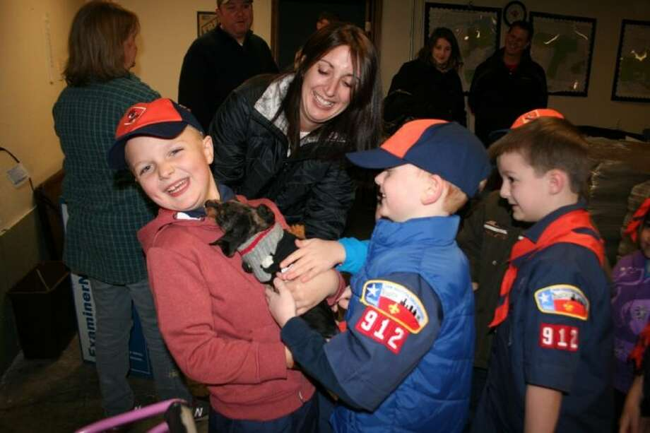 "Shown from left to right, Cub Scouts Jamie Gibson, Hayden Hallmark and Morgan Land pet the puppy ""Bo"" owned by Observer Newspapers Circulation Director Joann Clendenen. The puppy was in the warehouse where the scouts learned to roll and throw newspapers."