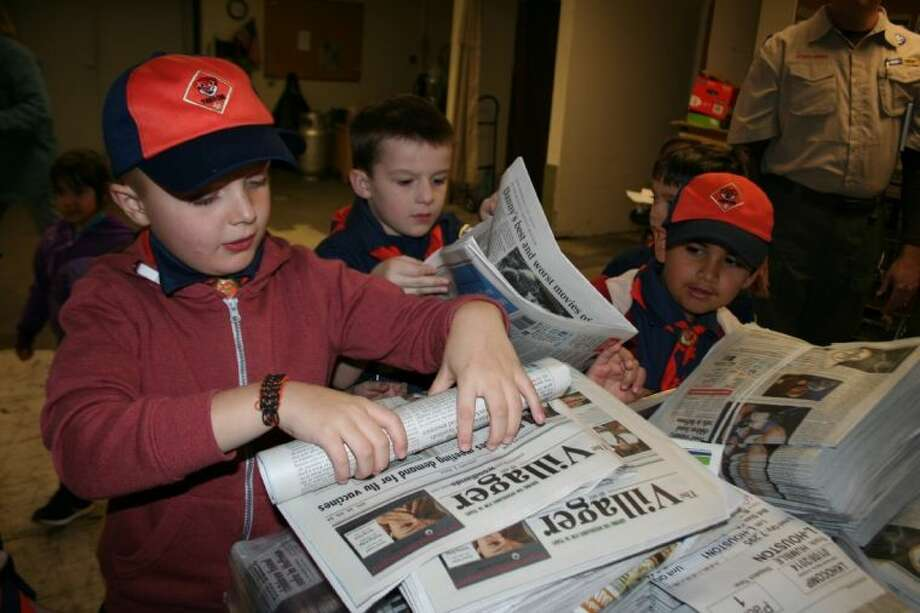 Shown from left to right, Cub Scouts Jamie Gibson, Morgan Land and Trey Gonzalez practiced rolling and bagging newspapers during their field trip to the Observer newspaper office Jan. 7. Photo: MELECIO FRANCO