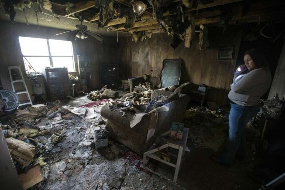 Family friend Christina Searcy looks over the living room after a grease fire broke out in Donnette Knox's kitchen Dec. 31, 2013, in Porter. The fire spread to most of the house through the ceiling leaving only two rooms in the home nearly untouched. The family has lived in the home for 31 years. Photo: ANDREW BUCKLEY