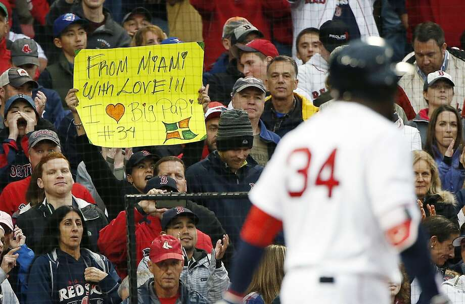 A fan holds a sign as Boston's David Ortiz comes to bat during the seventh inning at Fenway Park. Photo: Michael Dwyer, Associated Press
