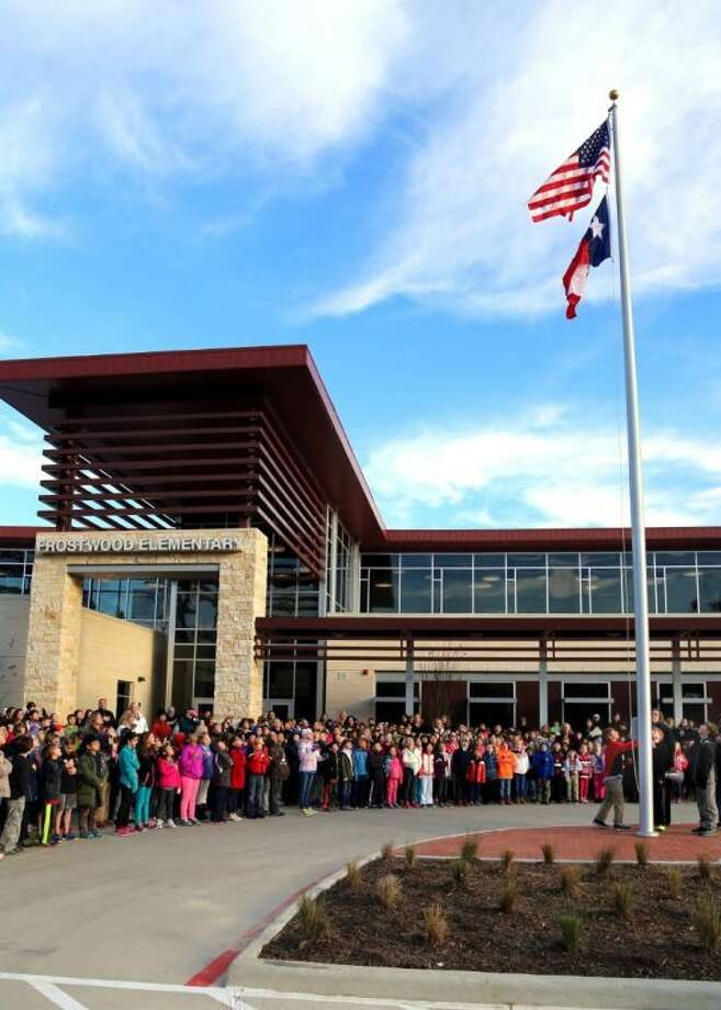 Frostwood students recite the pledge of allegiance as the flag is raised Tuesday morning. Photo: Rusty Graham