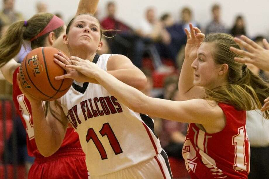 Huffman's Kelsie McEachern is fouled as she drives to the basket during Splendora's victory over Huffman last Friday at Hargrave High School. Photo: ANDREW BUCKLEY