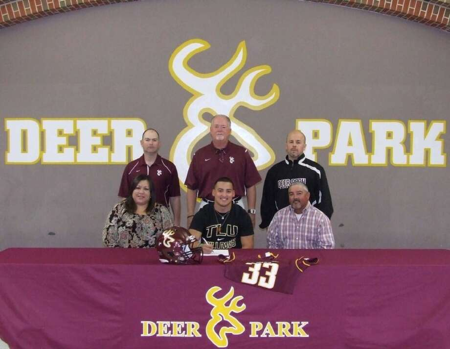 Senior Clay De La Garza recently signed his letter of intent to play football for Texas Lutheran University. He is pictured with his parents Karen and Joe De La Garza along with assistant coaches Nolan Patterson and Doug Bull, and head coach Chris Massey. Photo: Jeri Martinez