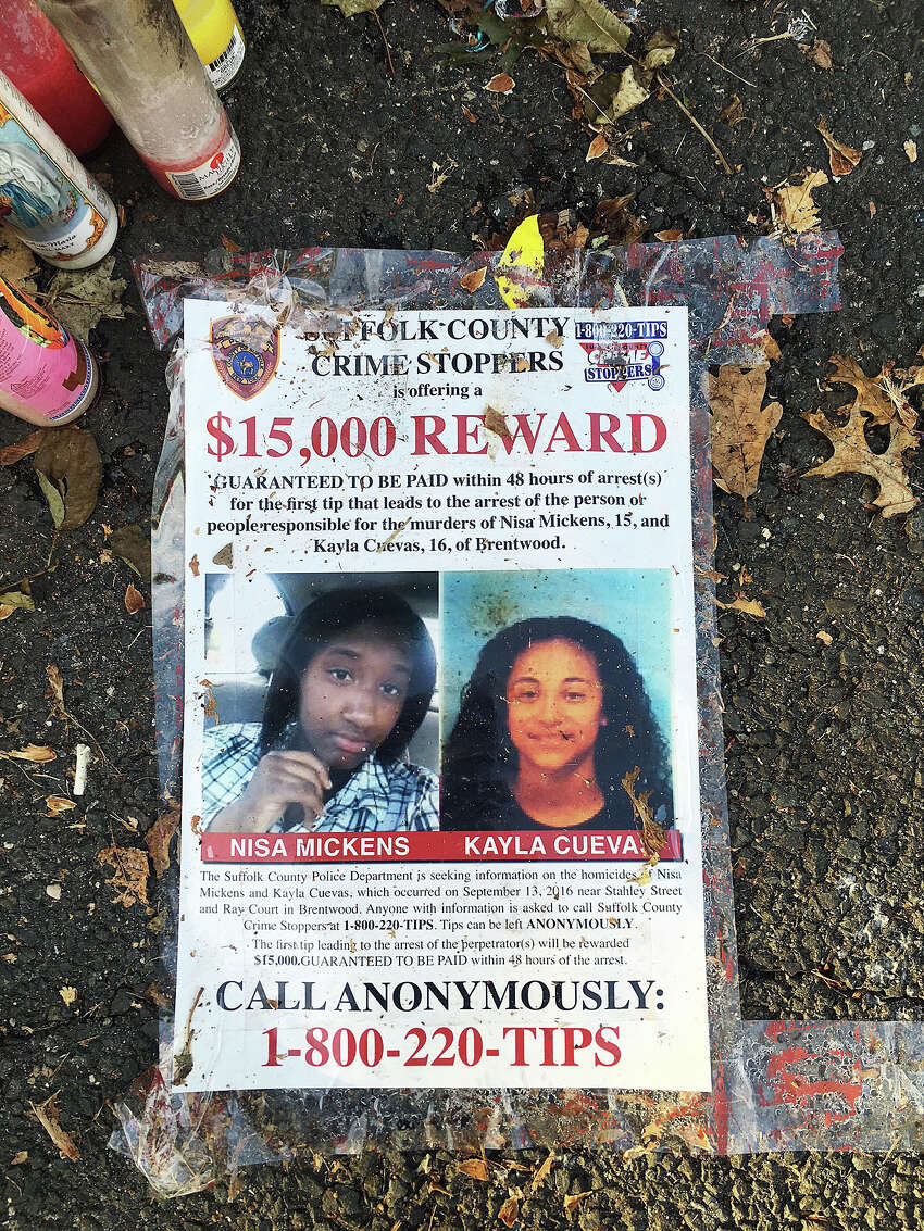 In this Sept. 27, 2016 photo, a poster featuring photos of Nisa Mickens and Kayla Cueva is part of a memorial near the spot where their bodies were found in Brentwood, N.Y. The girls, who were best friends, were found murdered. Multiple teenagers from the same Long Island high school have been found dead and while police suspect all the deaths are related to gang violence, they are releasing few details. (AP Photo/Claudia Torrens) ORG XMIT: RPCT101