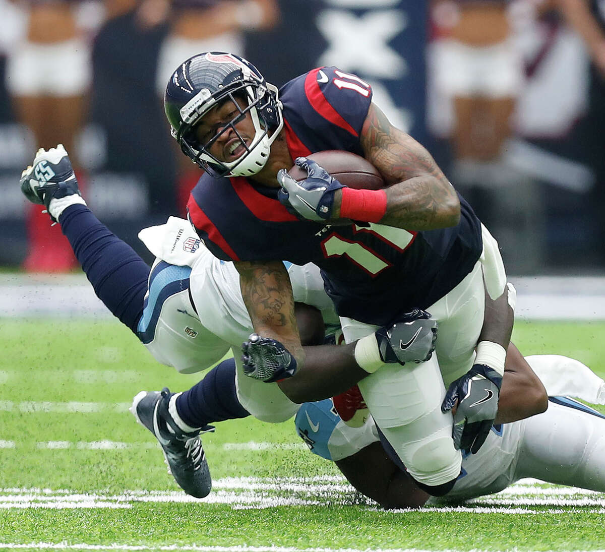 Houston Texans wide receiver Jaelen Strong (11) is brought down by Tennessee Titans linebacker Sean Spence (55) during the second quarter of an NFL football game at NRG Stadium, Sunday, Oct. 2, 2016 in Houston.