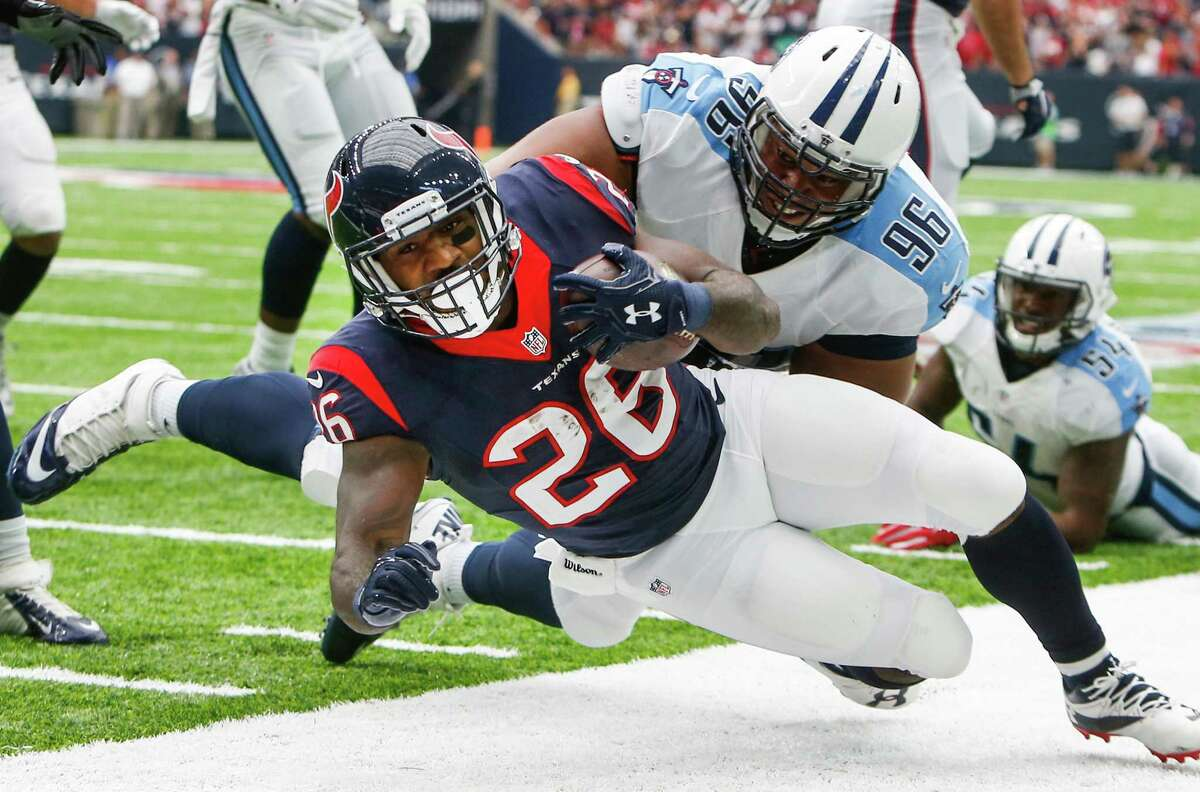 Texans running back Lamar Miller (26) is knocked out of bounds near the goal line by Tennessee nose tackle Al Woods (96) during the first quarter Sunday at NRG Stadium.