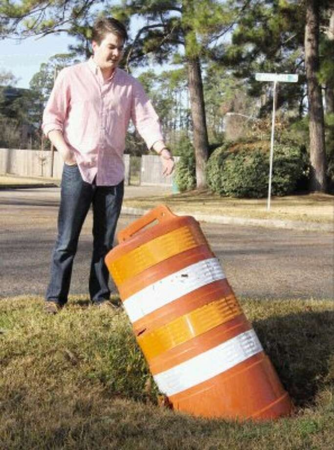 Kyle Grimmer shows a hole caused by a broken storm drain on his property off Sawdust Road Saturday. Photo: Staff Photo By Jason Fochtman